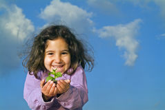 Little girl holding plant. Against cloudy blue sky Royalty Free Stock Image