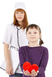 Little girl holding plush heart and pediatrician doctor woman be Stock Photo