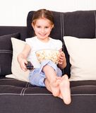Little girl watching TV. Little girl holding popcorn and watching TV Stock Photo