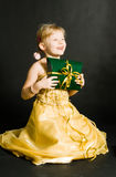 Little girl holding present. Little girl in yellow dress sitting and holding present stock photography