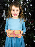 Little girl holding present with christmas tree behind Stock Images