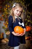 Little girl holding pumpkin in autumn interior stock photo