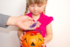 Little girl holding a pumpkin with candies in her hands, on Halloween. Grown-up people put candy to children in a pumpkin. stock photo