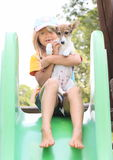 Little girl holding a puppy on a slide Royalty Free Stock Image
