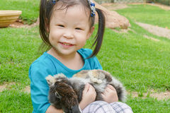 Little girl holding rabbit in park Royalty Free Stock Photography