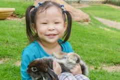Little girl holding rabbit in park Stock Photos