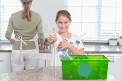 Little girl holding recycling bottles with thumbs up Stock Photo