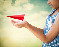 Little girl holding a red aircraft paper origami Royalty Free Stock Photo