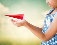 Little girl holding a red aircraft paper origami Stock Image