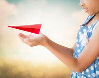 Little girl holding a red aircraft paper origami Royalty Free Stock Images