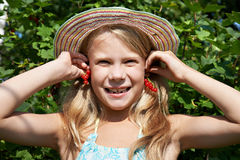 Little girl holding red currants near her ears Stock Photos