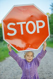 Little girl holding a red sign Royalty Free Stock Images