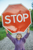 Little girl holding a red sign Stock Image