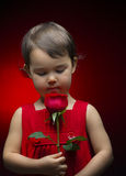 Little Girl holding rose  on red Royalty Free Stock Photos