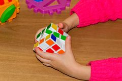 A little girl holding a Rubik& x27;s cube on a wood background. A little girl holding a Rubik& x27;s cube on a wood background Royalty Free Stock Photo