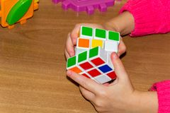 A little girl holding a Rubik's cube on a wood background. royalty free stock photography