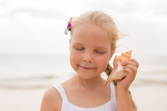 Little girl holding a seashell Royalty Free Stock Images