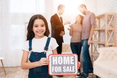 Little girl is holding sign with inscription. House for sale. Realtor shows apartment to couple. Stock Photo