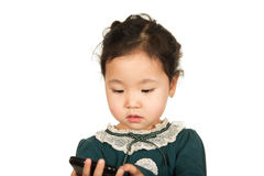 Little girl holding a smart phone and looking at it. Isolated on white background. Close-up Royalty Free Stock Photography