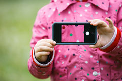 Little girl holding a smart phone with picture on display Stock Images