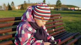 Little girl holding a smartphone while sitting on a park bench. Close up. stock footage