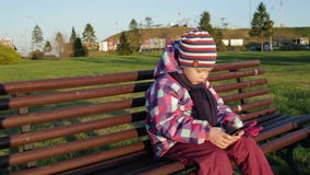 Little girl holding a smartphone while sitting on a park bench. stock footage