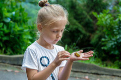 Little girl holding snail in hand Royalty Free Stock Photos