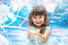 Little girl holding snow. A little girl holding snow on blue background Stock Image