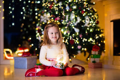 Little girl holding snow globe under Christmas tree Stock Images