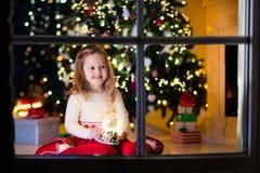 Little girl holding snow globe under Christmas tree Stock Photo