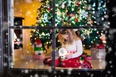 Little girl holding snow globe under Christmas tree Royalty Free Stock Image
