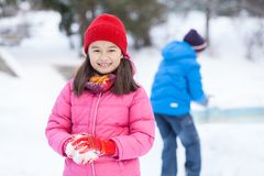 Little girl holding snowball and smiling. Stock Photography