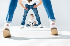 Little girl holding soccer ball with parents in front Stock Photo