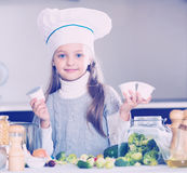 Little girl holding soft cheese in packs at kitchen Stock Photography