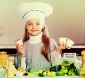 Little girl holding soft cheese in packs at kitchen Stock Photo