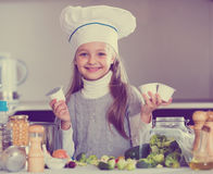 Little girl holding soft cheese in packs at kitchen Royalty Free Stock Photos