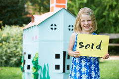 Little Girl Holding Sold Sign Outside Cardboard Playhouse Stock Photos