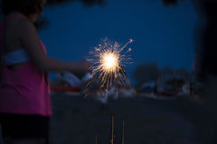 Little girl holding sparkler during outdoor celebration Stock Photo