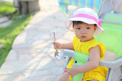 A little girl holding a spoon and sitting in her go-cart Stock Image