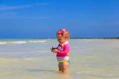 Little girl holding starfish at summer beach Royalty Free Stock Image