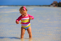 Little girl holding starfish at summer beach Royalty Free Stock Photography