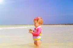 Little girl holding starfish at summer beach Royalty Free Stock Photo