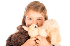 Little girl Holding stuffed animals. An adorable little girl holding three plush toys close to her face. Isolated on white Royalty Free Stock Photo