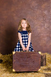 Little girl holding suitcase in retro style Stock Images