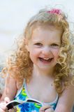 Little girl holding sunglasses. Adorable little curly haired girl wearing a bathing suit and holding a pair of sunglasses royalty free stock images