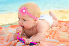 Little girl holding sunglasses on the sea shore.  Stock Photography