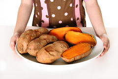 Little girl holding sweet potatoes on a plate Royalty Free Stock Image