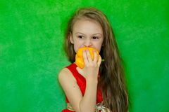 A little girl holding a sweet yellow pepper in her hand. stock photo