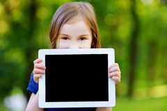Little girl holding tablet PC outdoors. Happy little girl holding tablet PC outdoors in summer park on beautiful sunny day Stock Image