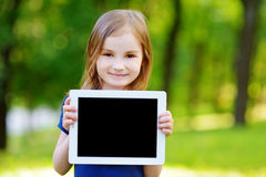 Little girl holding tablet PC outdoors Royalty Free Stock Photography